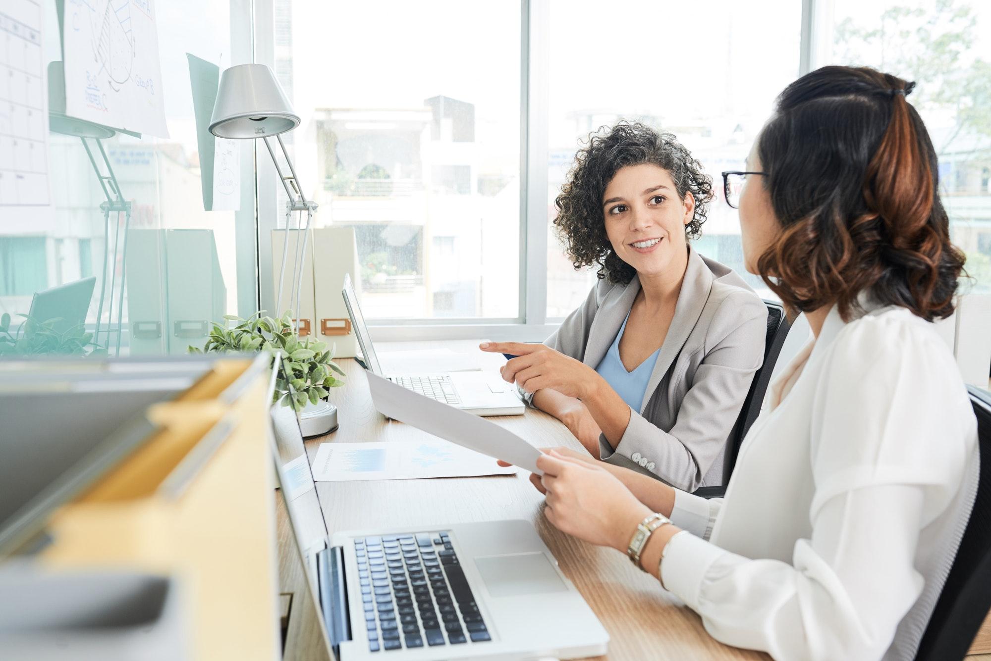 Businesswomen discussing documents